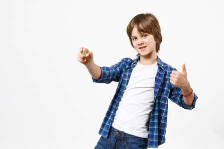 Fun little kid boy in blue t-shirt hold bitcoin, future currency showing thumbs up isolated on white wall background children studio portrait. People childhood lifestyle concept. Mock up copy space.