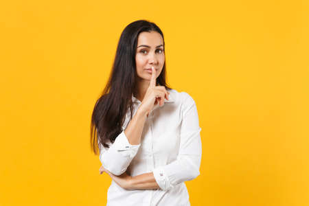 Portrait of attractive young woman in white shirt saying hush be quiet with finger on lips shhh gesture isolated on yellow orange background in studio. People lifestyle concept. Mock up copy space. 免版税图像