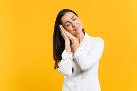Portrait of relaxed smiling young woman in white casual shirt sleep with folded hands under cheek isolated on yellow orange wall background in studio. People lifestyle concept. Mock up copy space.