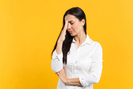 Portrait of crying upset young woman in white shirt keeping eyes closed, putting hand on nose isolated on bright yellow orange wall background in studio. People lifestyle concept. Mock up copy space.