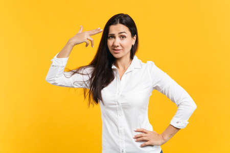Portrait of desperate young woman in white casual shirt point finger to head as if she about shoot herself isolated on yellow orange background in studio. People lifestyle concept. Mock up copy space.