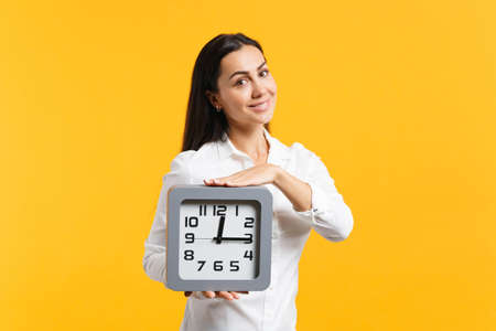 Portrait of smiling beautiful young woman in white casual shirt holding square clock, looking camera isolated on yellow orange wall background in studio. People lifestyle concept. Mock up copy space.