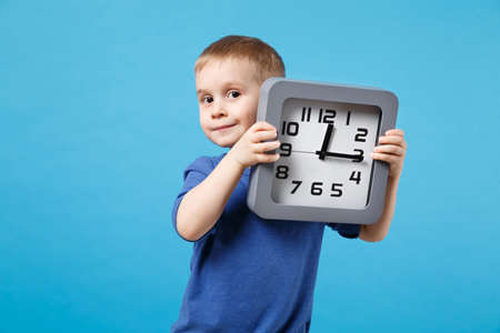 Smiling cute fun kid boy 4 years old wearing blue t-shirt clothes hold in hands clock isolated on blue wall background children studio portrait. People childhood lifestyle concept. Mock up copy space.