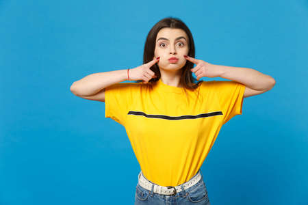 Portrait of funny young woman in vivid casual clothes looking camera pointing index finger on blowing cheeks isolated on bright blue background in studio. People lifestyle concept. Mock up copy space.
