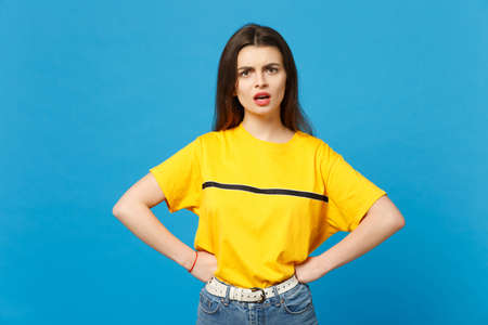 Portrait of bewildered irritated young woman in vivid casual clothes standing with arms akimbo on waist isolated on bright blue wall background in studio. People lifestyle concept. Mock up copy space.