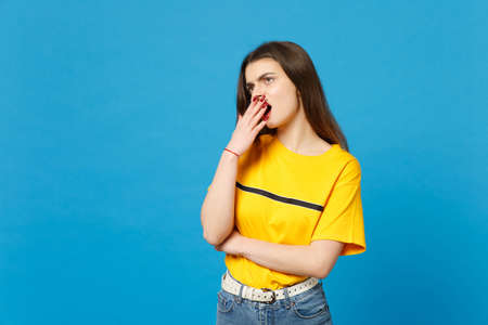 Portrait of tired boring young woman in vivid casual clothes looking aside up yawning covering mouth with hand isolated on blue wall background in studio. People lifestyle concept. Mock up copy space.