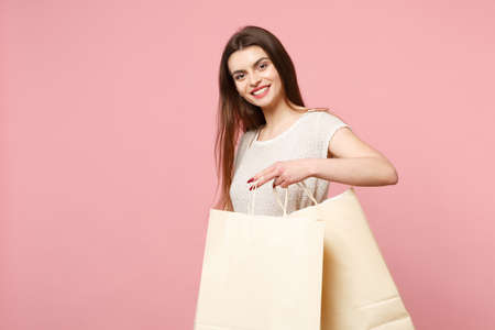 Smiling young woman in casual light clothes posing isolated on pastel pink background, studio portrait. People lifestyle concept. Mock up copy space. Holding package bag with purchases after shopping. Stock Photo