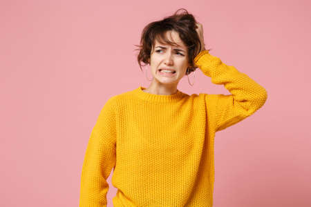 Preoccupied confused young brunette woman girl in yellow sweater posing isolated on pastel pink background in studio. People lifestyle concept. Mock up copy space. Looking aside, putting hand on head.