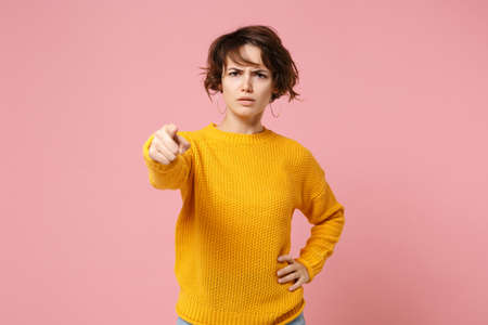 Strict displeased young brunette woman girl in yellow sweater posing isolated on pastel pink background, studio portrait. People lifestyle concept. Mock up copy space. Pointing index finger on camera.