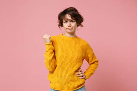 Displeased confused young brunette woman girl in yellow sweater posing isolated on pastel pink wall background in studio. People sincere emotions lifestyle concept. Mock up copy space. Clenching fist. Foto de archivo