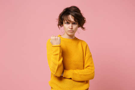 Angry irritated young brunette woman girl in yellow sweater posing isolated on pastel pink wall background in studio. People sincere emotions lifestyle concept. Mock up copy space. Clenching fist.