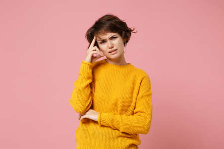 Preoccupied young brunette woman girl in yellow sweater posing isolated on pastel pink background, studio portrait. People sincere emotions lifestyle concept. Mock up copy space. Putting hand on head.