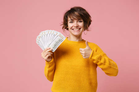 Smiling young brunette woman in yellow sweater posing isolated on pastel pink background. People lifestyle concept. Mock up copy space. Holding fan of cash money in dollar banknotes, showing thumb up.