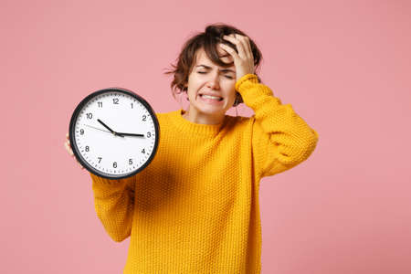 Preoccupied young brunette woman girl in yellow sweater posing isolated on pastel pink wall background. People sincere emotions lifestyle concept. Mock up copy space. Holding clock, put hand on head.