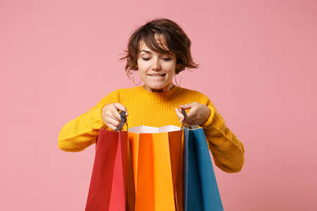 Pretty young brunette woman girl in yellow sweater posing isolated on pink wall background in studio. People lifestyle concept. Mock up copy space. Holding package bag with purchases after shopping.