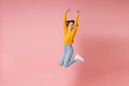 Cheerful young brunette woman girl in yellow sweater posing isolated on pastel pink background in studio. People lifestyle concept. Mock up copy space. Having fun fooling around rising hands, jumping. Banco de Imagens