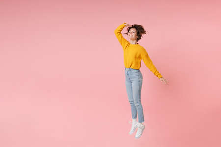 Smiling young brunette woman girl in yellow sweater posing isolated on pastel pink background. People lifestyle concept. Mock up copy space. Jumping holding hand at forehead looking far away distance. Banco de Imagens