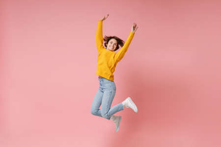 Smiling young brunette woman girl in yellow sweater posing isolated on pastel pink background in studio. People lifestyle concept. Mock up copy space. Having fun fooling around, rising hands, jumping.