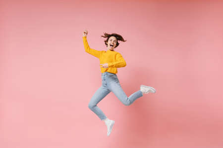 Excited young brunette woman girl in yellow sweater posing isolated on pastel pink background in studio. People lifestyle concept. Mock up copy space. Having fun fooling around, rising hands, jumping. Banco de Imagens