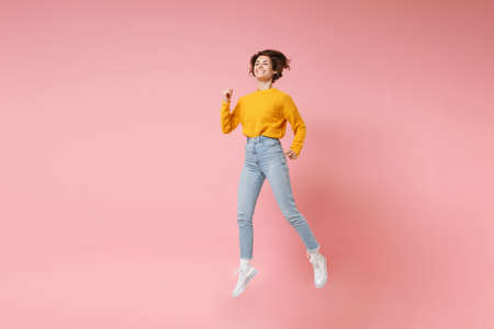 Funny young brunette woman girl in yellow sweater posing isolated on pastel pink background in studio. People lifestyle concept. Mock up copy space. Having fun fooling around, looking aside, jumping.
