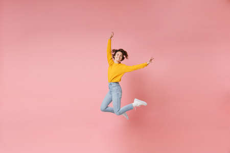 Funny young brunette woman girl in yellow sweater posing isolated on pastel pink background in studio. People lifestyle concept. Mock up copy space. Having fun, fooling around, rising hands, jumping.