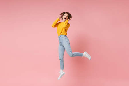 Cheerful laughing young brunette woman girl in yellow sweater posing isolated on pastel pink wall background in studio. People lifestyle concept. Mock up copy space. Having fun fooling around jumping.