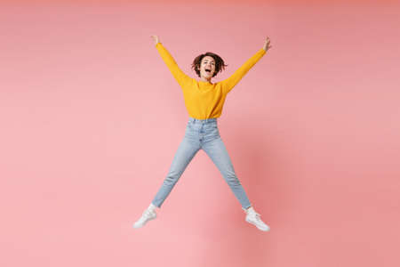 Funny young brunette woman girl in yellow sweater posing isolated on pastel pink background. People lifestyle concept. Mock up copy space. Having fun fooling around, spreading hands and legs, jumping. Banco de Imagens