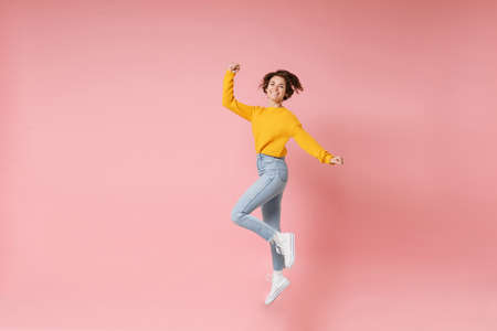 Joyful young brunette woman girl in yellow sweater posing isolated on pastel pink wall background. People lifestyle concept. Mock up copy space. Having fun fooling around jumping doing winner gesture.