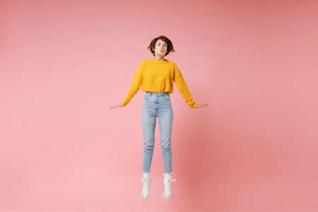 Pretty young brunette woman girl in yellow sweater posing isolated on pastel pink background in studio. People lifestyle concept. Mock up copy space. Having fun spreading hands rising hands, jumping. Banco de Imagens