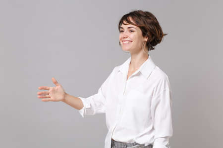Smiling young business woman in white shirt posing isolated on gray background in studio. Achievement career wealth business concept. Mock up copy space. Standing with outstretched hand for greeting Banque d'images