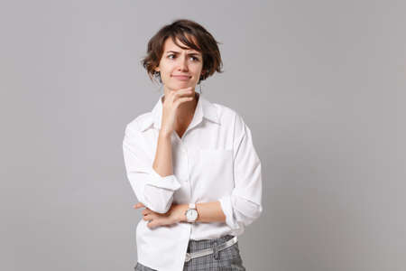 Confused young business woman in white shirt posing isolated on gray wall background in studio. Achievement career wealth business concept. Mock up copy space. Put hand prop up on chin, looking aside