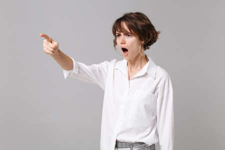 Angry nervous young business woman in white shirt posing isolated on gray background in studio. Achievement career wealth business concept. Mock up copy space. Pointing index finger on aside swearing