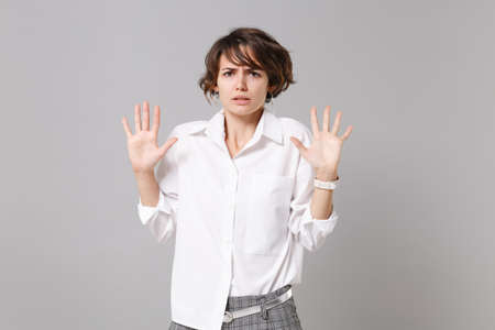 Concerned bewildered young business woman in white shirt posing isolated on gray background in studio. Achievement career wealth business concept. Mock up copy space. Rising hands up, showing palms