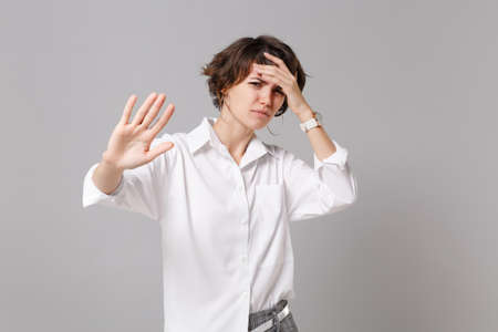 Tired young business woman in white shirt posing isolated on gray background in studio. Achievement career wealth business concept. Mock up copy space. Showing stop gesture with palm put hand on head