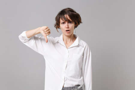 Displeased dissatisfied young business woman in white shirt posing isolated on gray wall background studio portrait. Achievement career wealth business concept. Mock up copy space. Showing thumb down
