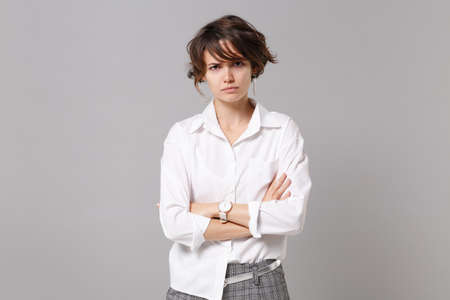 Dissatisfied displeased young business woman in white shirt posing isolated on gray wall background in studio. Achievement career wealth business concept. Mock up copy space. Holding hands crossed
