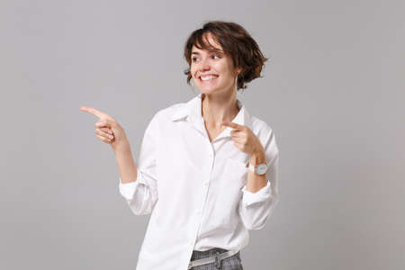 Smiling cute young business woman in white shirt posing isolated on gray wall background studio portrait. Achievement career wealth business concept. Mock up copy space. Pointing index fingers aside Banque d'images