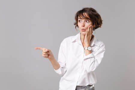 Amazed young business woman in white shirt posing isolated on gray background in studio. Achievement career wealth business concept. Mock up copy space. Put hand on cheek, pointing index finger aside Banque d'images