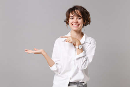 Smiling young business woman in white shirt posing isolated on gray wall background, studio portrait. Achievement career wealth business concept. Mock up copy space. Pointing index finger, hand aside Banque d'images