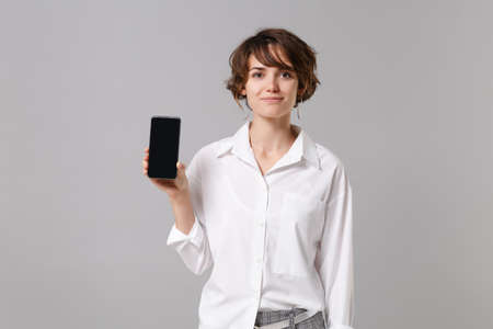 Smiling young business woman in white shirt posing isolated on gray background in studio. Achievement career wealth business concept. Mock up copy space. Holding mobile phone with blank empty screen