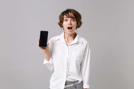 Shocked young business woman in white shirt posing isolated on gray background in studio. Achievement career wealth business concept. Mock up copy space. Holding mobile phone with blank empty screen