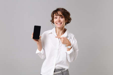 Pretty business woman in white shirt posing isolated on gray background. Achievement career wealth business concept. Mock up copy space. Pointing index finger on mobile phone with blank empty screen