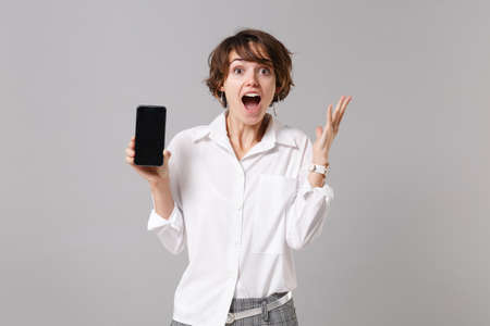 Excited business woman in white shirt posing isolated on gray background. Achievement career wealth business concept. Mock up copy space. Spreading hands, hold mobile phone with blank empty screen Banque d'images