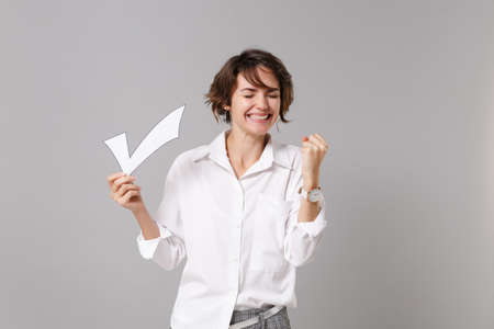 Happy young business woman in white shirt posing isolated on grey wall background in studio. Achievement career wealth business concept. Mock up copy space. Hold paper check mark doing winner gesture. Banque d'images