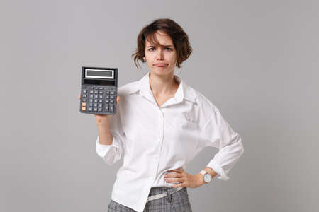 Displeased confused young business woman in white shirt posing isolated on grey background studio portrait. Achievement career wealth business concept. Mock up copy space. Holding in hand calculator. Imagens
