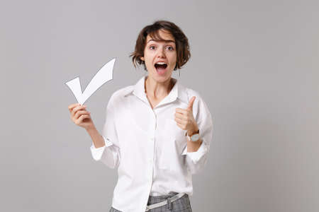 Excited young business woman in white shirt posing isolated on grey background studio portrait. Achievement career wealth business concept. Mock up copy space. Hold paper check mark, showing thumb up.