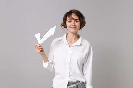 Smiling attractive young business woman in white shirt posing isolated on grey wall background studio portrait. Achievement career wealth business concept. Mock up copy space. Hold paper check mark.