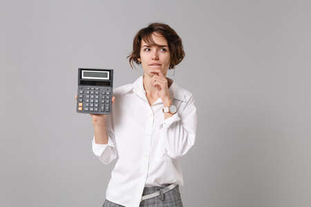 Pensive young business woman in white shirt posing isolated on grey wall background in studio. Achievement career wealth business concept. Mock up copy space. Hold calculator put hand prop up on chin.