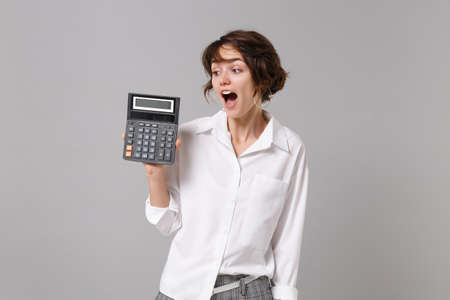 Excited young business woman in white shirt posing isolated on grey wall background studio portrait. Achievement career wealth business concept. Mock up copy space. Hold calculator keeping mouth open.