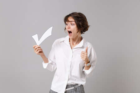 Shocked young business woman in white shirt posing isolated on grey background studio portrait. Achievement career wealth business concept. Mock up copy space. Hold paper check mark, showing thumb up.